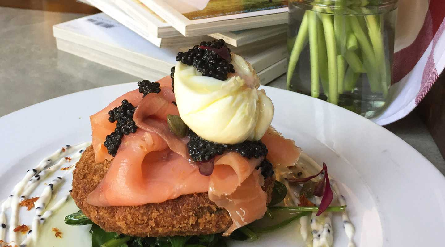Perfectly soft poached egg with smoked salmon and caviar on a crispy potato cake