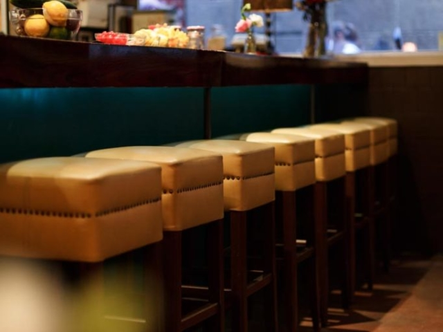 Yellow studded stools to compliment the teal coloured walls.